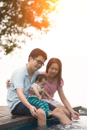 mom dad: Familia asiática que se divierten en la piscina