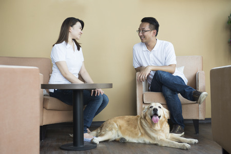 asian couple at cafe with their pets Stock Photo