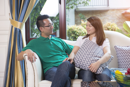 couple on couch: asian couple in indoor setting