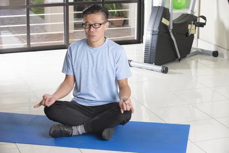 man meditating: Asian man meditating indoor Stock Photo