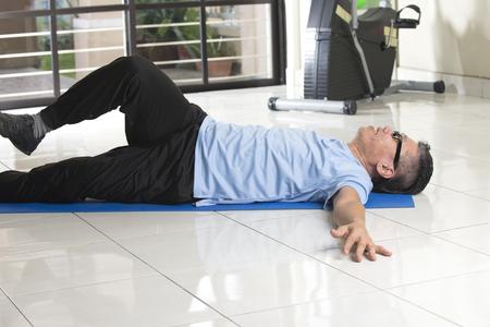 ropa deportiva: Hombre asiático en ropa deportiva haciendo estiramiento de la pierna