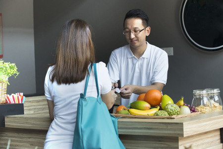 asian girl paying bills  for grocery to sales man