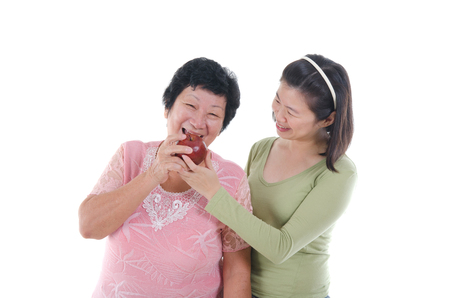 asian senior male having appl with her  daughter photo
