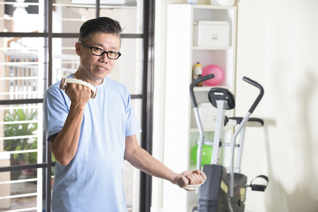 man gym: asian senior male with dumbell in the gym Stock Photo