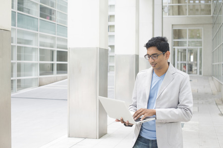 indian male with laptop at outdoor office Stock Photo