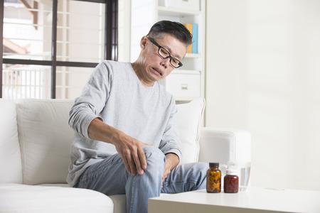 seniors suffering painful illness: asian senior male with knees pain