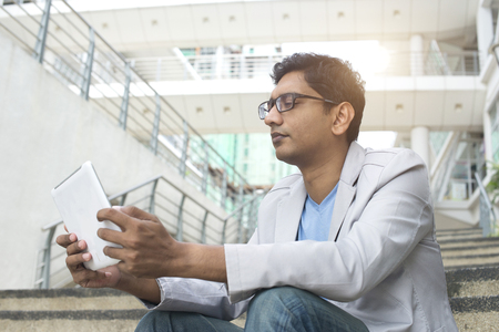 african student: indian male using tablet outdoor