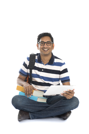 specs: indian young male student surfing while sitting on the floor