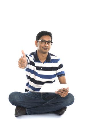 specs: smiling indian male surfing while sitting on the floor Stock Photo