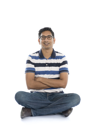 indian style sitting: Happy Indian man looking at camera. Isolated on white background