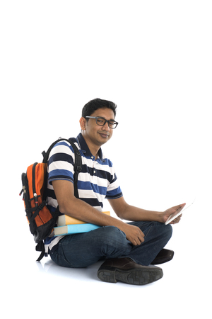 boy sitting: indian young male student surfing while sitting on the floor