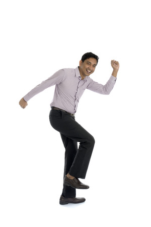 jump suit: Excited Indian businessman jumping for joy. Isolated on white background.