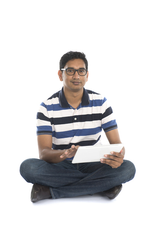 indian business man: smiling indian male surfing while sitting on the floor Stock Photo