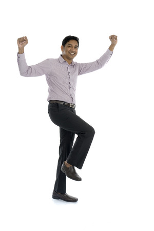 Excited Indian businessman jumping for joy. Isolated on white background. Stock Photo