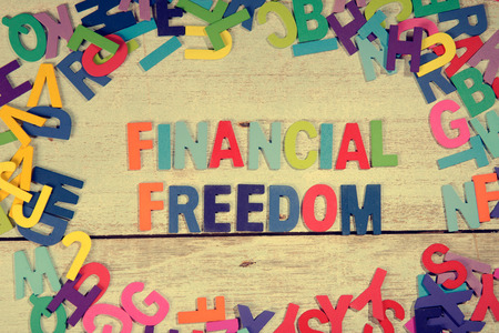 financial freedom: financial freedom word block concept photo on plank wood
