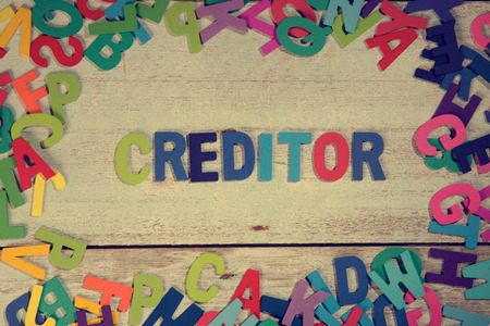 creditor: creditor word block concept photo on plank wood