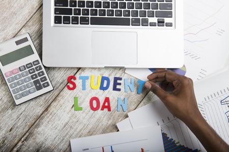 to arrange: Hand arrange wood letters as student Loan word