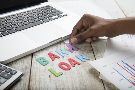 to arrange: Hand arrange wood letters as bank Loan word