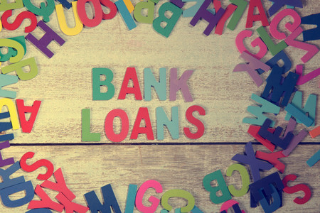 loans: bank loans word block concept photo on plank wood