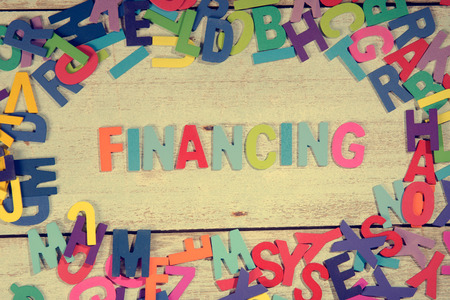 financing word block concept photo on plank wood