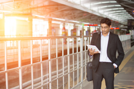 railroad station: indian business male using tablet computer while waiting for train Stock Photo