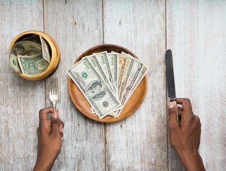 avid: hand eating banknotes symbolising consumerism and corruption