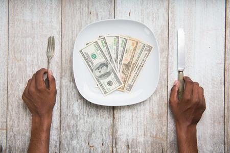 avid: eating banknotes symbolising consumerism and corruption