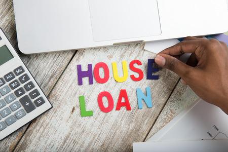 home finance: hand arranging house loan concept photo
