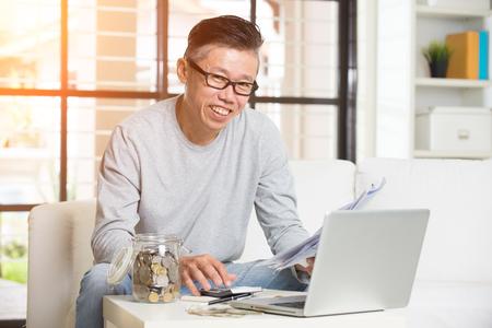 paying bills online: asian matured male paying bills online