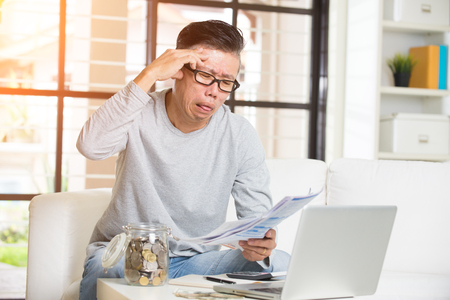 paying bills online: asian matured male paying bills online looking worried