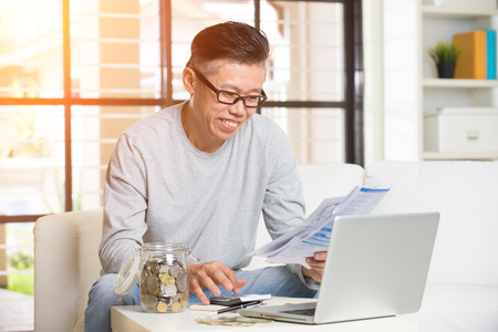 happy asian people: asian matured male paying bills online