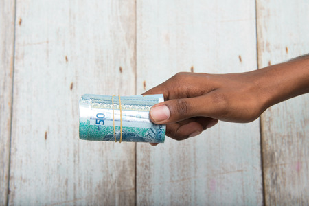 handing: Handing out money in Malaysia ringgit , dark tone skin