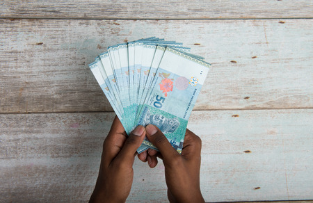 Handing out money in Malaysia ringgit , dark tone skin