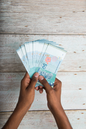 hand hold: Handing out money in Malaysia ringgit , dark tone skin