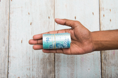 hold on: Handing out money in Malaysia ringgit , dark tone skin