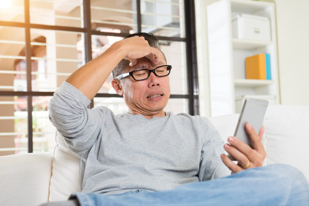 sore eye: asian male with illness when using too much gadgets