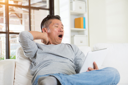 senior man on a neck pain: asian male with neck pain when using too much gadgets Stock Photo
