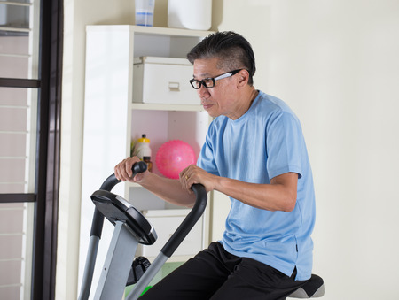 matured: matured asian male on exercise bike Stock Photo