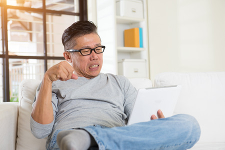 too much: asian male with hand pain when using too much gadgets Stock Photo