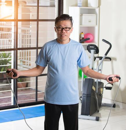 hombre deportista: madurado masculina asiática que hace saltar a la cuerda