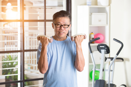 asian senior male with dumbell in the gym Stock Photo