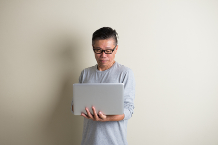 matured: matured asian male using laptop