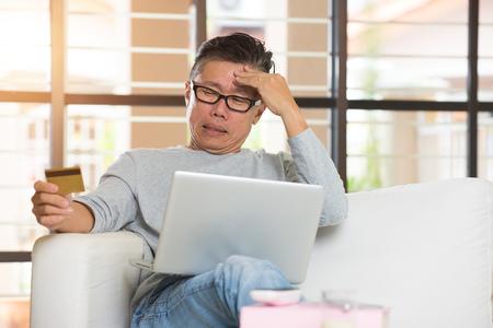 pagando: asiático de sexo masculino mayor que tiene problemas para hacer compras en línea con tarjeta de crédito