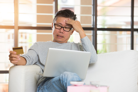 paying: asian senior male having trouble shopping online with credit card Stock Photo