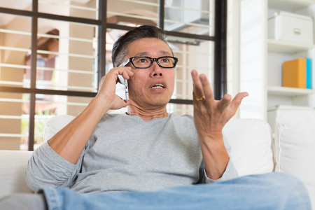 helplessness: depressed matured asian man on the phone Stock Photo