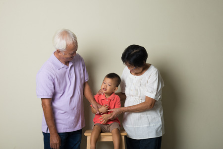 grandkids: Portrait Of Chinese Grandparents With Grandson  At Home Together Stock Photo