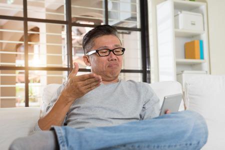 bad feeling: depressed matured asian man on the phone Stock Photo