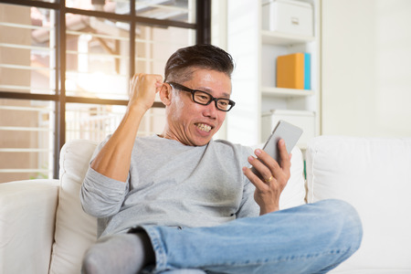 asian adult: Happy asian senior man using the mobile phone at home