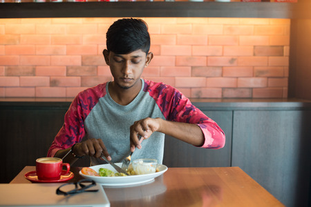 eating salad: teenage indian male eating at cafe Stock Photo