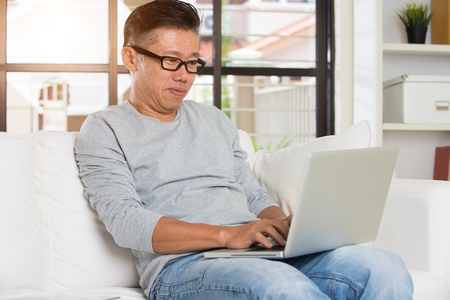 middle age: Man in living room with laptop smiling